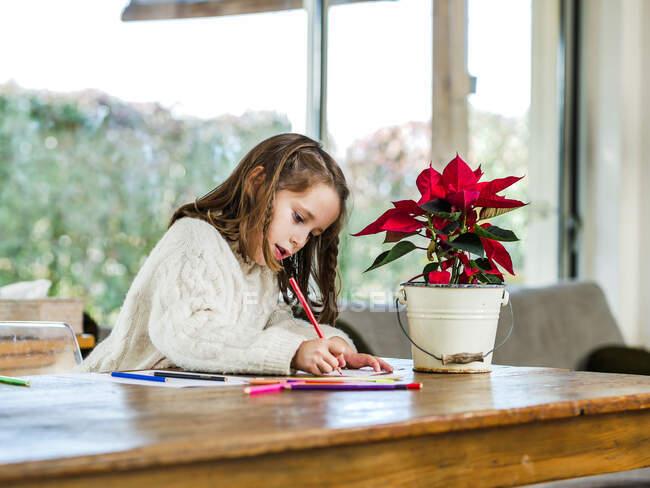 Ritagliare disegno bambina con matite multicolore su foglio di carta in stanza luce — Foto stock