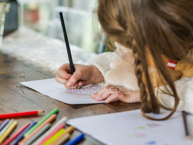 Crop anonymous little girl drawing with multicolored pencils on paper sheet in light room — Stock Photo