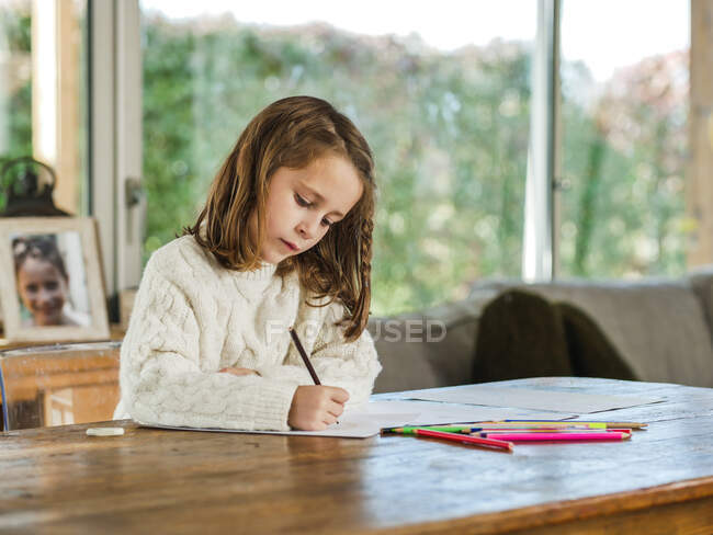 Crop little girl drawing with multicolored pencils on paper sheet in light room — Stock Photo