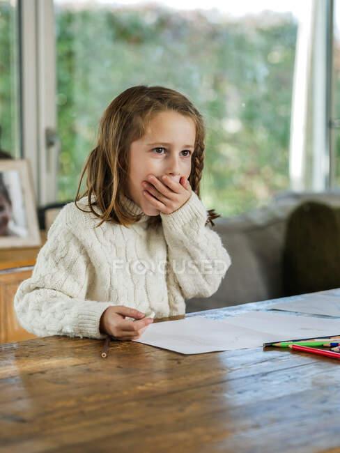 Симпатичная маленькая девочка в белом свитере закрывает рот рукой и смотрит в сторону, сидя за столом и рисуя карандашами — стоковое фото