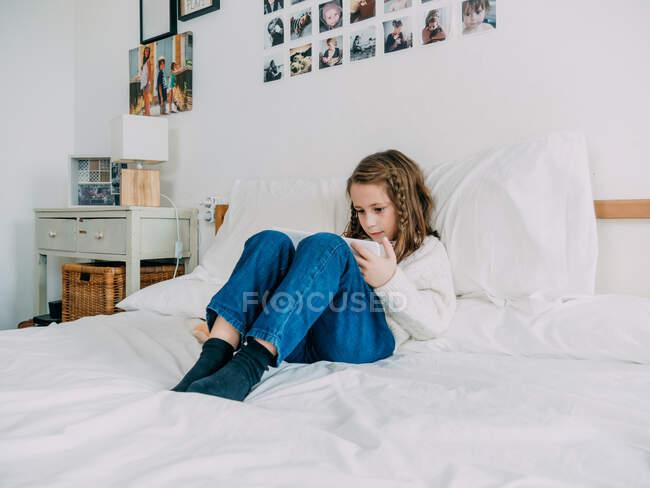 Девочка в повседневной одежде лежит на удобной кровати и смотрит видео на современном планшете в светлой спальне — стоковое фото