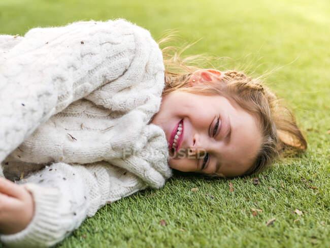 Adorable niña alegre vistiendo suéter blanco acogedor acostado en el prado herboso y mirando a la cámara con sonrisa - foto de stock