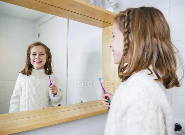 Vista lateral menina feliz vestindo camisola branca aconchegante olhando no espelho com sorriso de dente enquanto está com escova de dentes no banheiro moderno — Fotografia de Stock