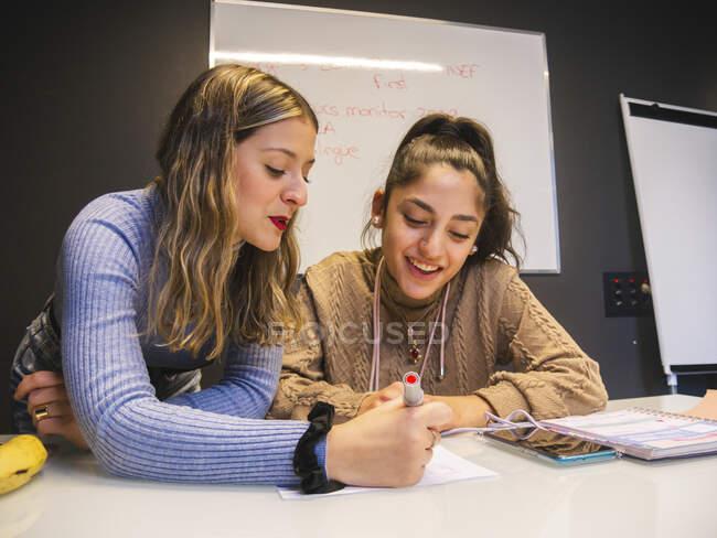 Studente con pennarello che spiega le informazioni per sorridere compagno di classe mentre si lavora su compiti insieme contro lavagna bianca — Foto stock