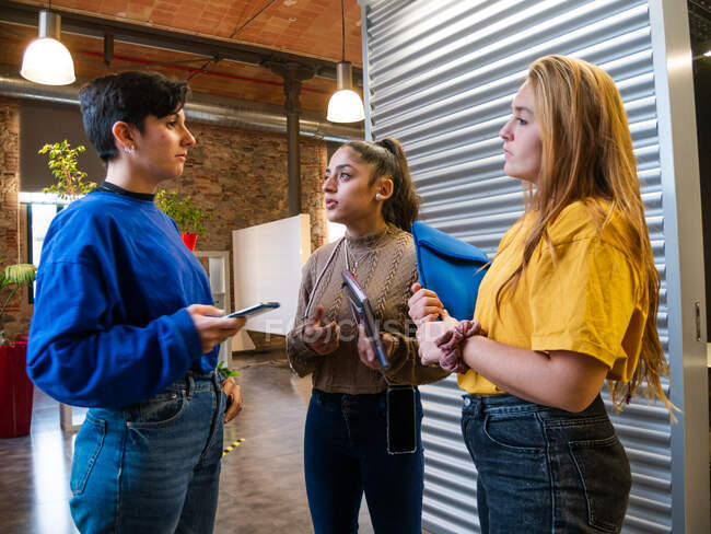 Young female classmates in casual wear standing close while talking about studying in corridor of university — Stock Photo