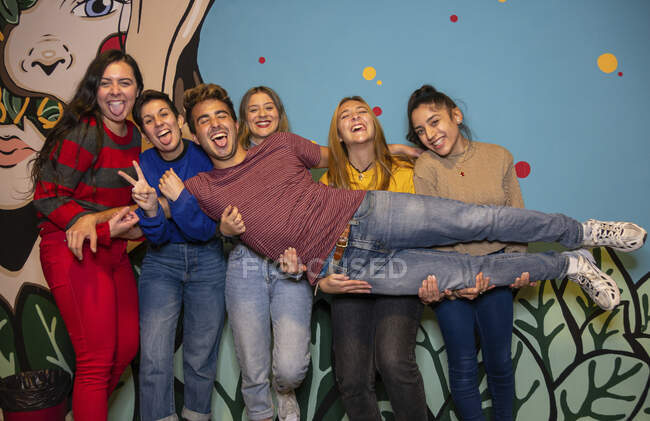 Group of excited young friends holding man with tongue out on hands while standing together against bright wall — Stock Photo