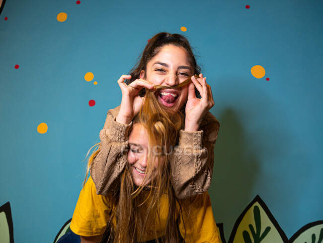 Positive female playing with hair while having fun with friend against colorful wall — Stock Photo