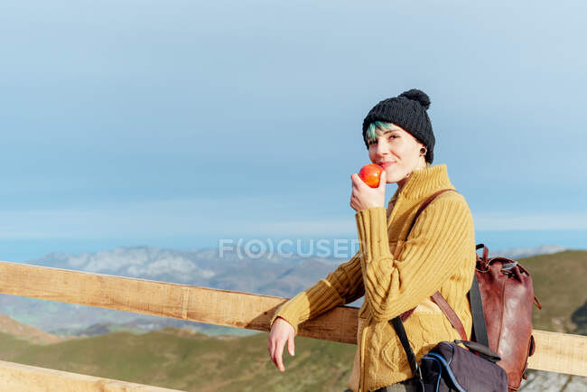 Side view glad young female traveler in warm sweater and hat standing with red apple on bridge and looking at camera while spending vacation in vast mountainous countryside — Stock Photo