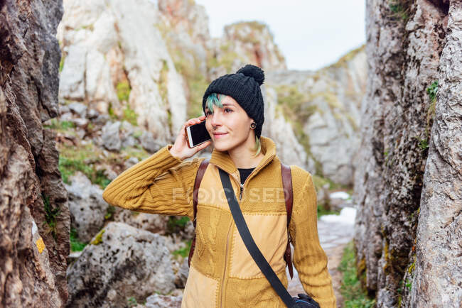 Mujer joven positiva en ropa casual y sombrero respondiendo a una llamada telefónica mientras está de pie en medio de formaciones rocosas y mirando hacia otro lado contenta — Stock Photo
