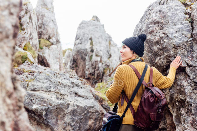 Back view content female traveler wearing warm clothes and hat standing amidst rough rocks and looking away in pleasant thoughts — Stock Photo