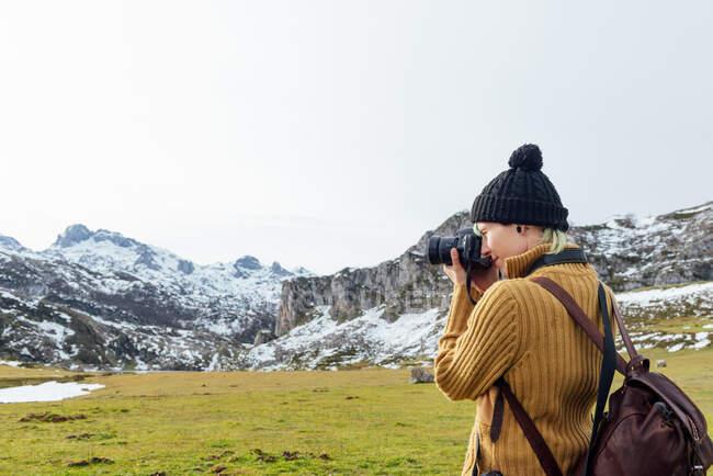 Vista laterale focalizzata giovane fotografo femminile in maglione caldo scattare foto su macchina fotografica professionale di maestose montagne grezze su altopiano erboso sulla chiara giornata autunnale — Foto stock