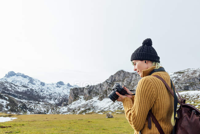 Side view focused young female photographer in warm sweater taking pictures on professional photo camera of majestic rough mountains on grassy highland on clear autumn day — Stock Photo