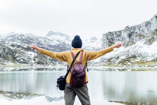 Невідома жінка-мандрівниця стоїть з витягнутими руками на холодному озері і милується суворими скелястими горами, вкритими снігом в зимовий день. — стокове фото