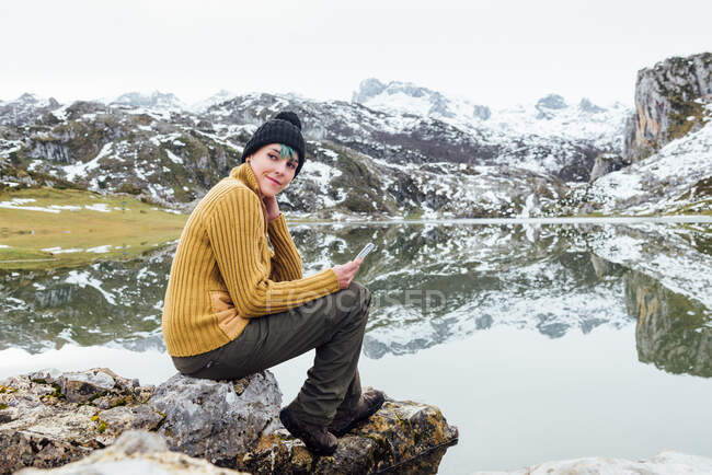 Side view full body young glad female wearing warm sweater and hat using mobile phone and looking away while sitting on sharp stony lake shore surrounded by severe snowy mountains — Stock Photo