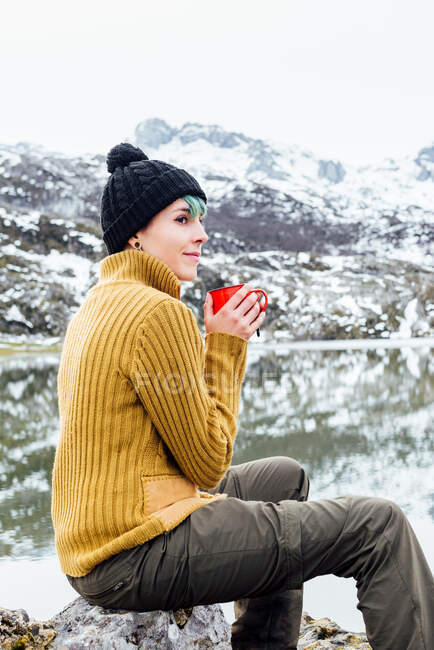 Side view tranquil young female in warm sweater and hat drinking hot beverage while sitting on sharp stone on cold lake shore surrounded by rough severe snowy mountains — Stock Photo
