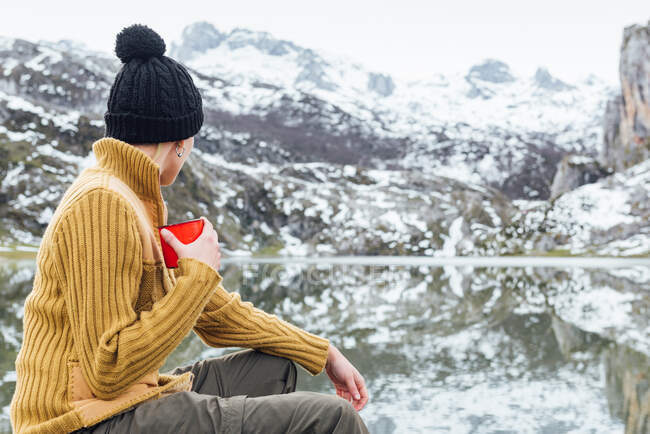 Back view of anonymous tranquil young female in warm sweater and hat drinking hot beverage while sitting on sharp stone on cold lake shore surrounded by rough severe snowy mountains — Stock Photo