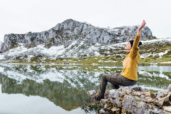 Female wearing warm sweater and black hat sitting with arms outstretched on rough stone on tranquil lakeside with closed eyes near landscape of snowy rocky mountains — Stock Photo