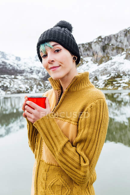 Portrait of tranquil young female in warm sweater and hat holding hot beverage in front of snowy mountains — Stock Photo