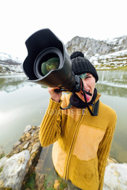 Female photographer wearing warm clothes and hat shooting pictures and looking at camera while standing on lakeside surrounded by rough snowy mountains — Stock Photo