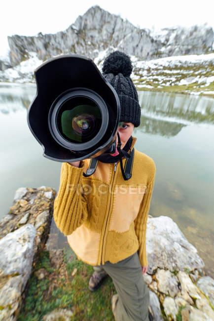 Женщина-фотограф в теплой одежде и шляпе снимает фотографии и смотрит в камеру, стоя на берегу озера в окружении грубых снежных гор — стоковое фото