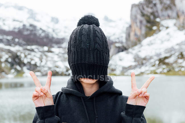Anonymous female hiding face behind black hat and showing v sign while standing on snowy rough highlands on lake shore — Stock Photo
