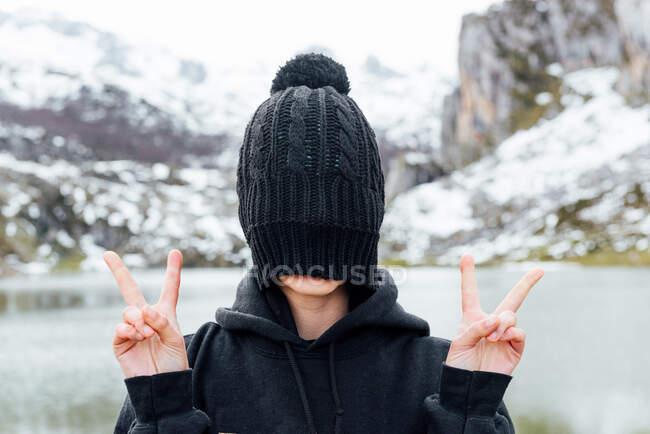 Anonimo volto femminile nascosto dietro il cappello nero e mostrando segno v mentre in piedi su altipiani innevati grezzi sulla riva del lago — Foto stock