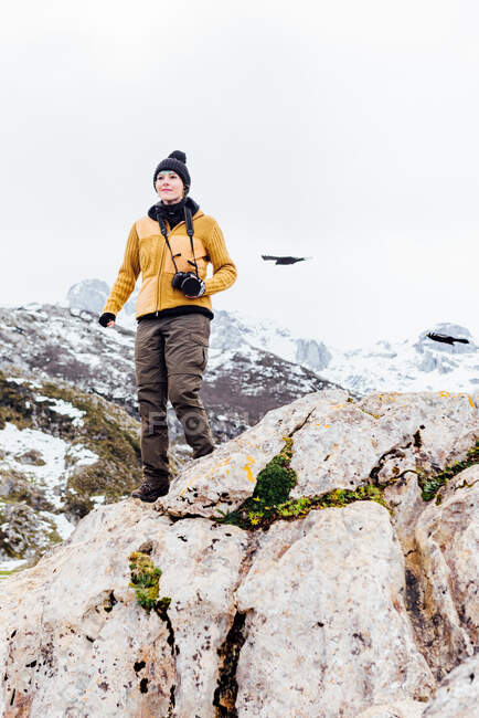 Fotografo donna a corpo intero in abiti caldi con macchina fotografica e in piedi su roccia dura ruvida in altopiani innevati nelle Asturie — Foto stock