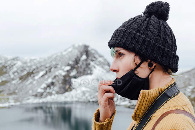 Side view serene young female traveler in warm hat lowering face mask and looking away in contemplation while standing on cold lake coast against majestic snowy mountain ridge — Stock Photo