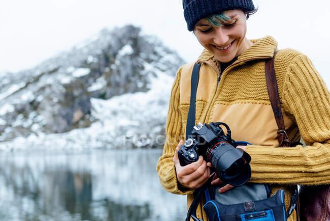 Giovane fotografa femminile in maglione caldo scattare foto su macchina fotografica professionale di maestose montagne grezze nella chiara giornata invernale — Foto stock