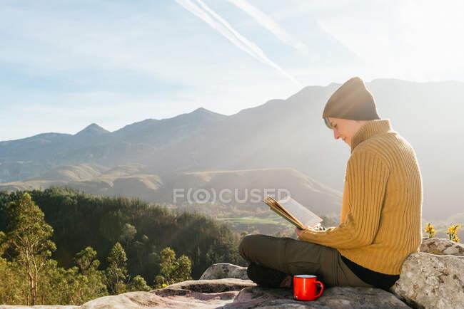 Seitenansicht des Inhalts weibliche Reisende sitzt mit einer Tasse Heißgetränk und liest interessante Buch vor dem Hintergrund der spektakulären Berglandschaft an sonnigen Tag — Stockfoto