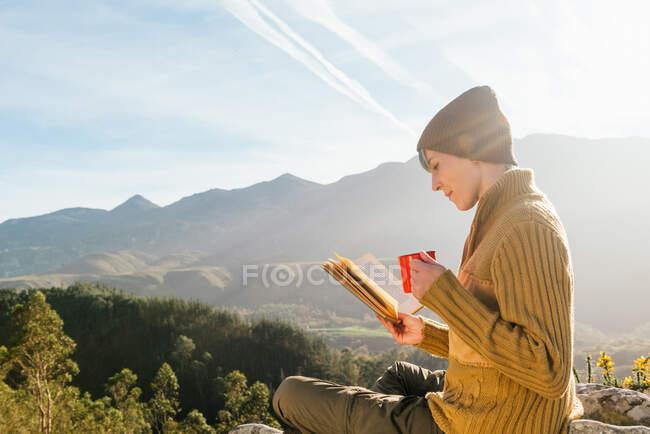 У сонячний день жінка сидить з чашкою гарячого напою і читає цікаву книжку на задньому плані мальовничого гірського краєвиду. — стокове фото