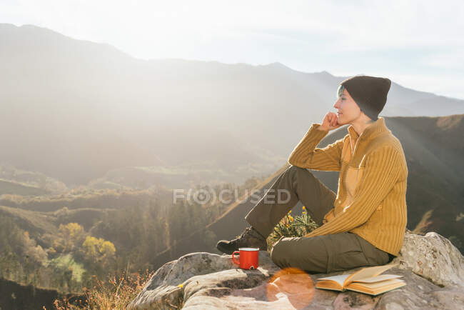 У сонячний день жінка - мандрівник сидить з чашкою гарячого напою і читає цікаву книжку на тлі мальовничого гірського краєвиду. — стокове фото