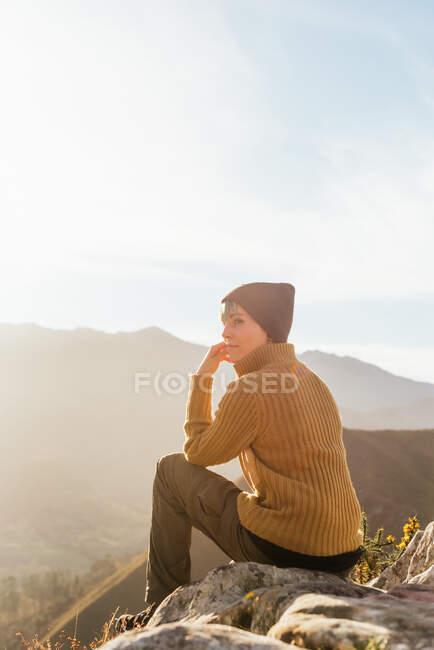 Vista lateral do caminhante sentado em pedra e observando paisagens incríveis do vale das terras altas no dia ensolarado — Fotografia de Stock