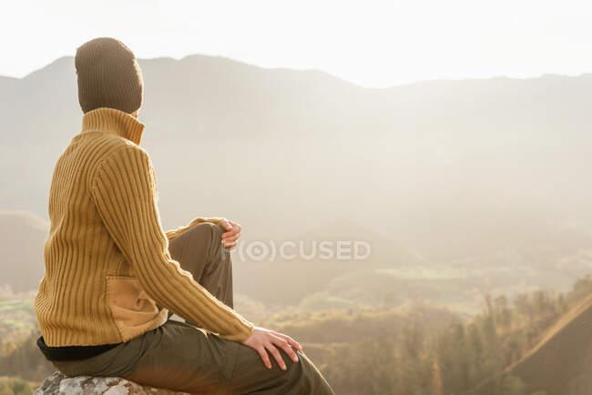 Vista lateral de un excursionista irreconocible sentado en piedra y observando increíbles paisajes del valle de las tierras altas en un día soleado - foto de stock