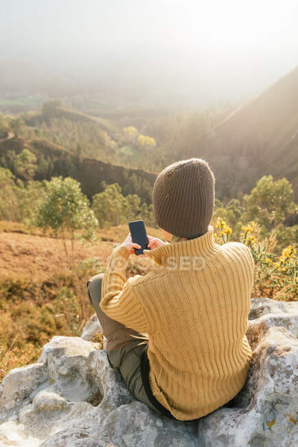 Back view of female explorer messaging on mobile phone while sitting on background of mountain range on sunny day — Stock Photo