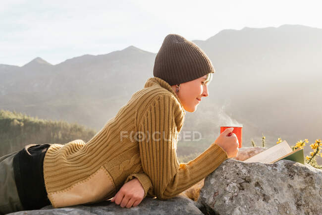 Side view of content female traveler lying with cup of hot drink and reading interesting book on background of spectacular mountainous landscape on sunny day — Stock Photo