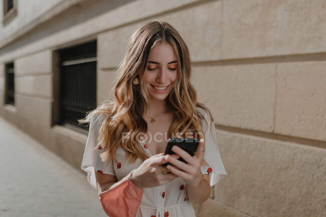 Young candid focused female in ornamental apparel with mask and cellphone on urban pavement — Stock Photo