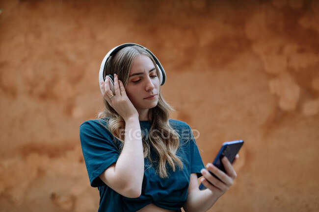 Young focused female in wireless headset text messaging on cellphone while standing with raised leg near wall in town on brown background — Stock Photo