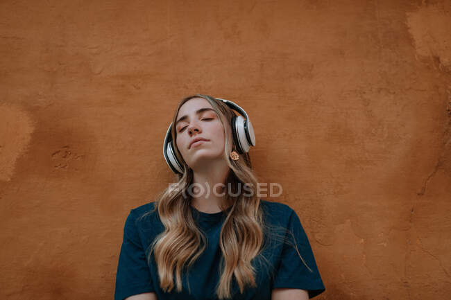 Young mindful blonde female with closed eyes listening to song in wireless headset on brown background in city — Stock Photo