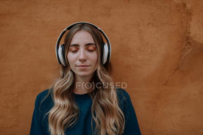 Jeune femme blonde consciente avec les yeux fermés écoutant la chanson dans un casque sans fil sur fond brun en ville — Photo de stock
