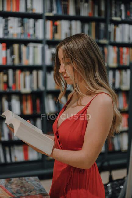 Бічний погляд на молоду жінку в червоному сонцезахисному сукні з відкритим підручником стоїть у книгарні. — стокове фото