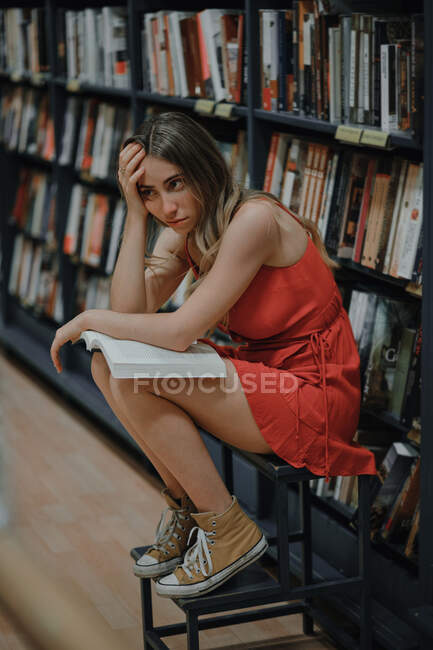 Vue latérale de la jeune femme épuisée en tenue de soleil et des gommes touchant le front tout en étant assis avec le manuel et regardant loin dans la librairie — Photo de stock