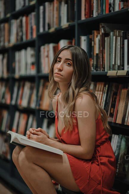 У сонячному вбранні молода безпристрасна жінка сидить з підручником і дивиться на камеру в книжковому магазині. — стокове фото