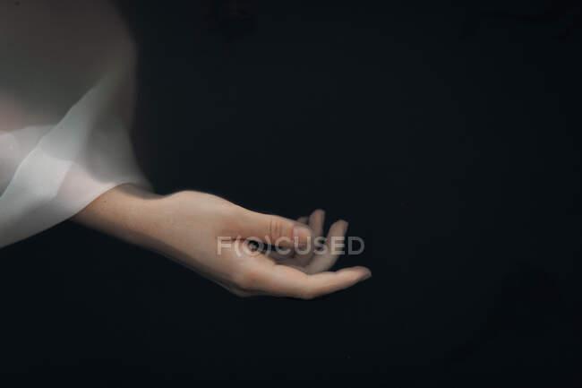 Da sopra raccolto sottile mano femminile in manica traslucida bianco bagnato galleggiante in acqua di lago scuro — Foto stock
