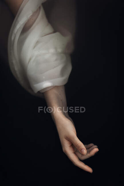 From above crop slim female hand in wet white translucent sleeve floating in dark lake water — Stock Photo