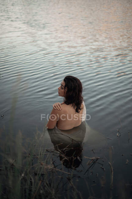 Back view of unrecognizable female traveler in fabric reflecting in pure lake water against trees during trip — Stock Photo