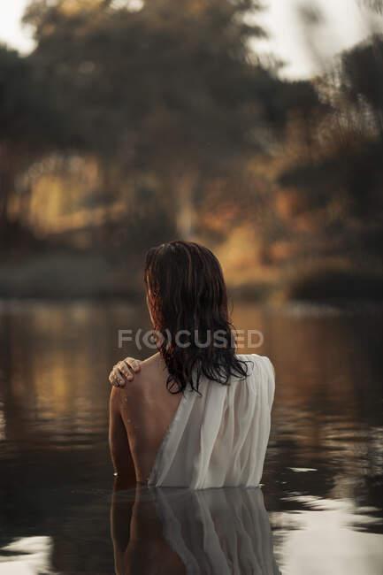 Vista posterior de viajera femenina irreconocible en tela que refleja en agua pura del lago contra los árboles durante el viaje - foto de stock