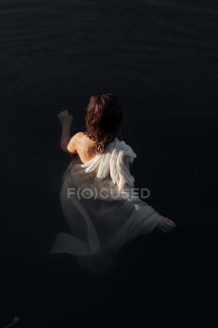 Back view of unrecognizable female in lake water during trip — Stock Photo