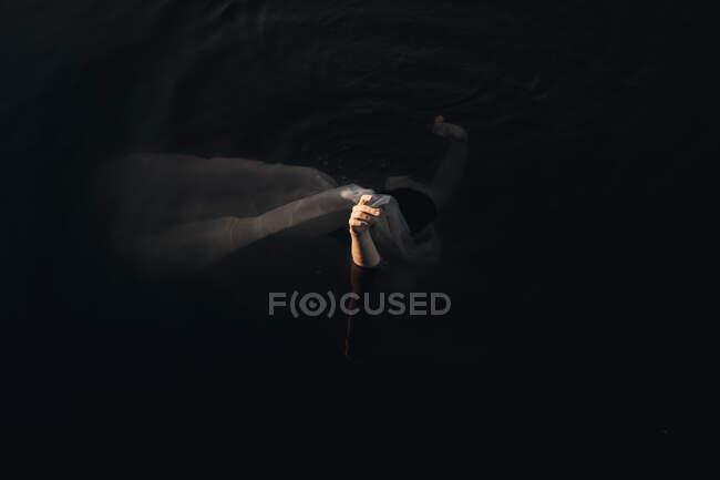 Desde arriba vista lateral de una mujer viajera irreconocible cubriendo la cara con textiles mientras está de pie con los brazos levantados en el agua al atardecer - foto de stock