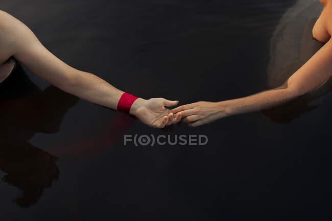 Dall'alto di viaggiatore anonimo di raccolto in braccialetto che tiene la mano di ragazza in lago puro — Foto stock